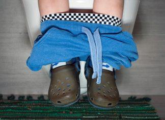Kind sitzt auf Toilette
