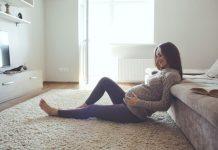 Sitzende Schwangere hält ihren Bauch