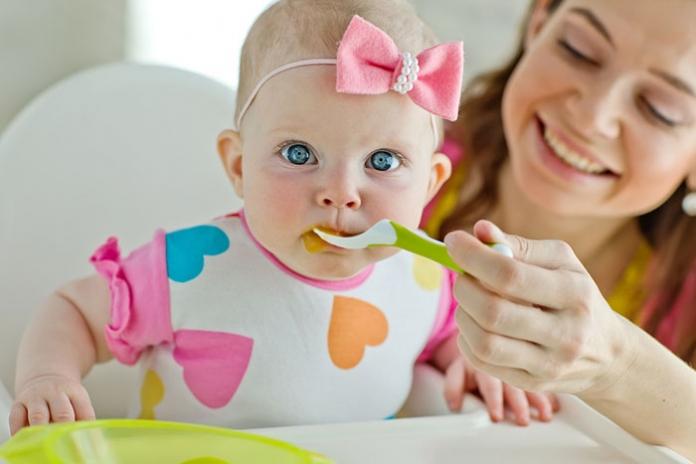 Mutter füttert Baby mit Brei