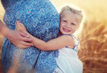 Kind umarmt schwangere Frau