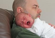 Vater hält schreiendes Baby