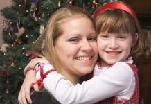 Mutter mit Kid vor dem Weihnachtsbaum