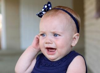 Kleinkind hält sich Ohr