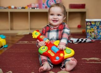 lachendes Baby mit Spielzeug-Gitarre