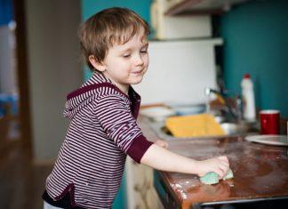 Kind putzt die Arbeitsfläche in der Küche