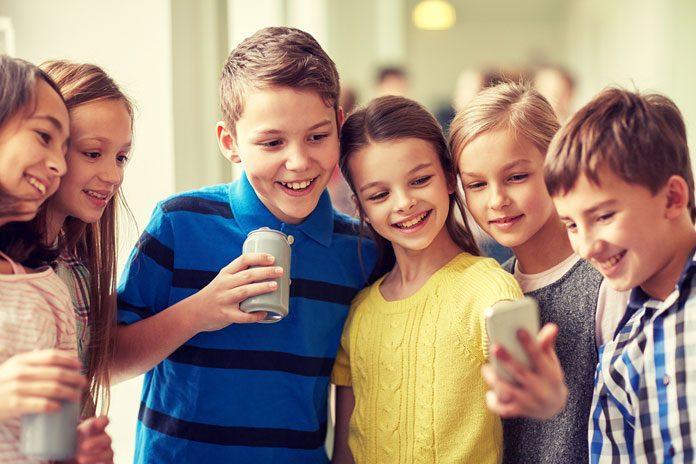 Schulkinder schauen auf ein Handy