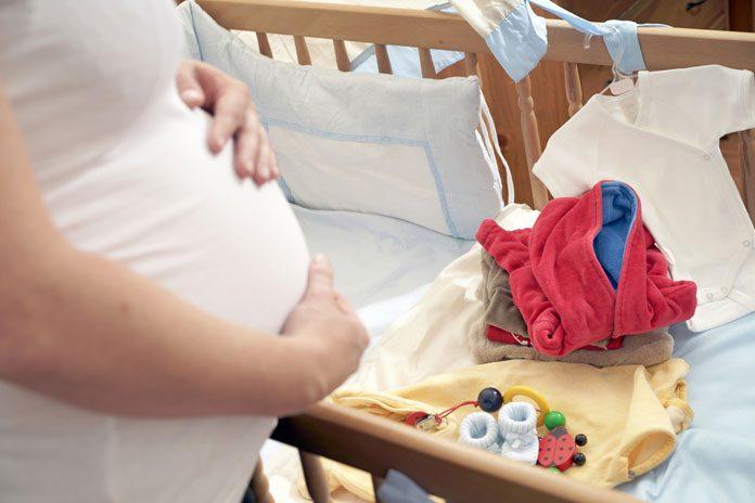 Schwangere mit Erstausstattung fürs Baby