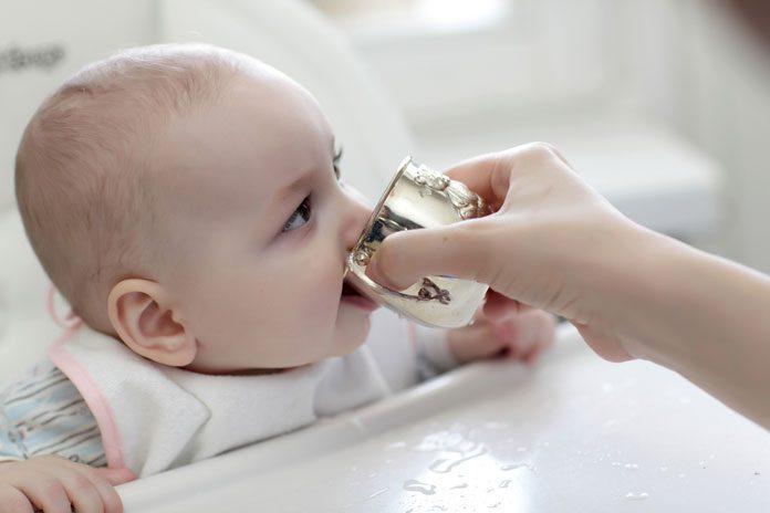 Baby trinkt aus Becher