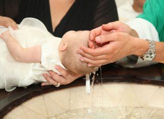 Baby wird über das Taufbecken gehalten und getauft