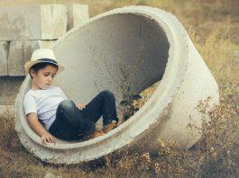 Kind sitzt in Betonreifen