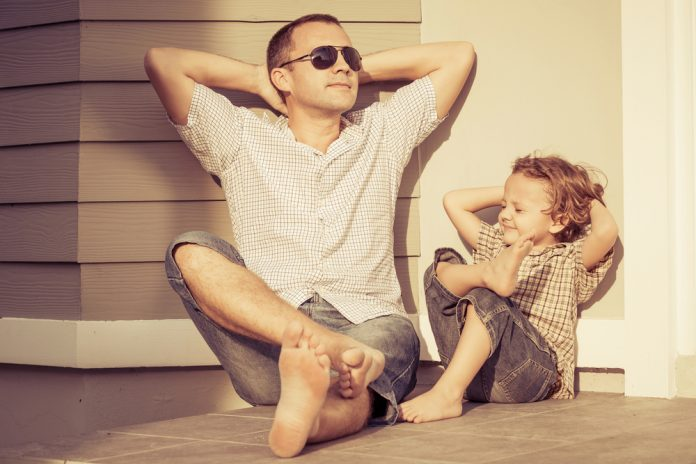 Vater und Kind sitzen entspannt auf dem Boden