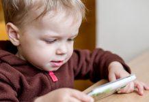 Kind spielt mit Handy Kinderfotos im Netz