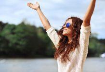Frau streckt Arme der Sonne entgegen
