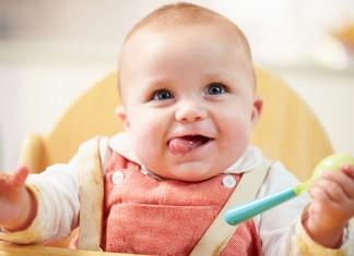 Baby im Hochstuhl mit Löffel