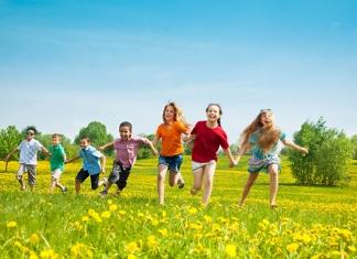 Fröhliche Kinder laufen über eine Wiese