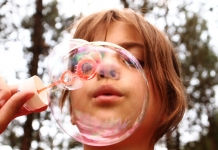 Kind bläst eine Seifenblase