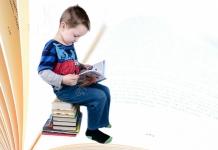 Kind sitz auf einem Stapel Bücher