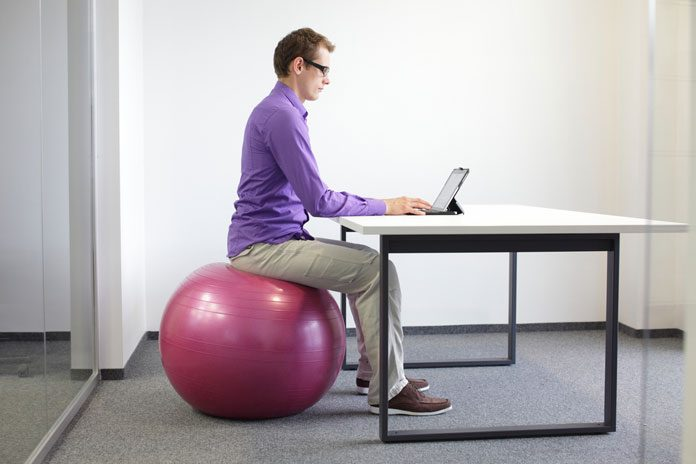 Mann sitzt auf einem Pezziball