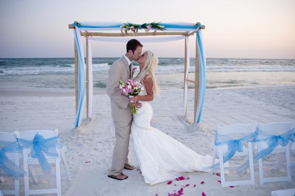 Brautpaar küsst sich bei Hochzeit am Strand